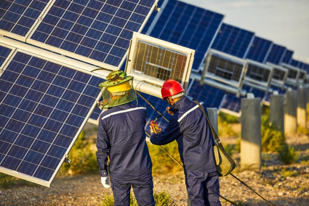Asian engineer patrolling solar photovoltaic area under the setting sun